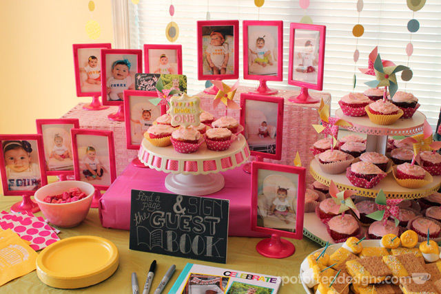 Pinwheel first birthday party: Monthly Photos displayed on dessert table in frames with @Krylon spray paint #birthdayparty | spotofteadesigns.com