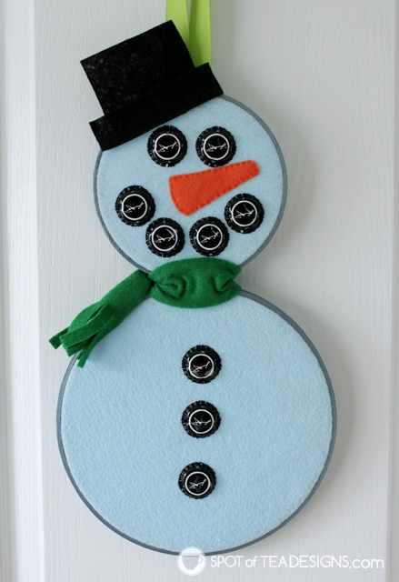 Mixed media snowman wall art - turn embroidery hoops, felt and bottle caps into winter wall art! | spotofteadesigns.com